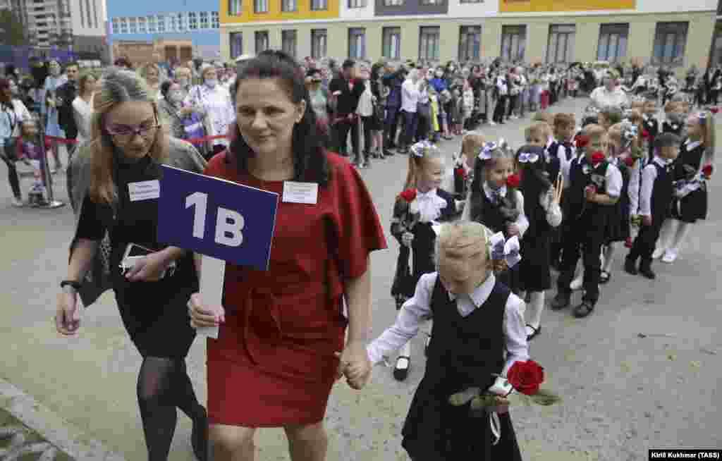 1 вересня першокласники присутні на урочистій церемонії початку нового навчального року в школі в російському Новосибірську. У Росії маски не є обов'язковими, але влада впроваджує низку інших протоколів зі збереження здоров'я