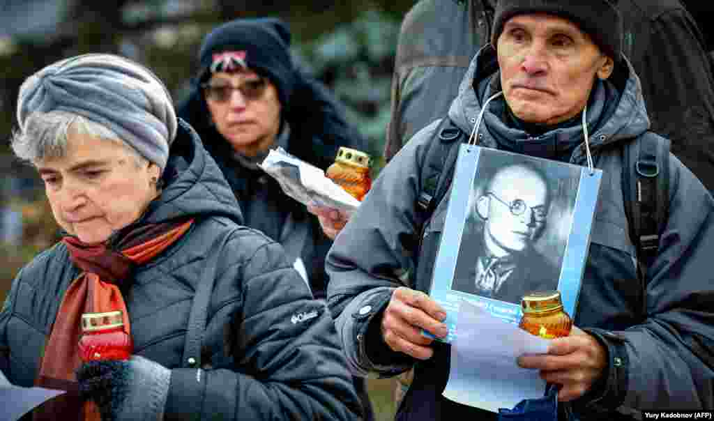 People carry candles and a picture near the Solovki Stone monument in front of the Federal Security Service building in central Moscow on October 29. (AFP/Yury Kadobnov)