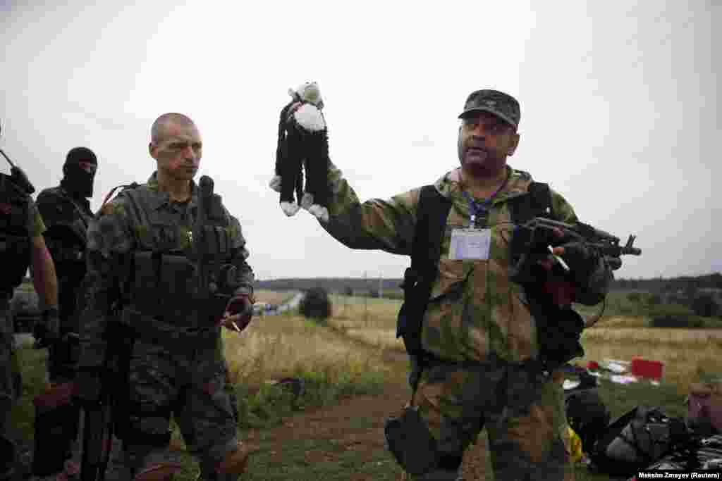 A pro-Russian separatist holds a child's stuffed toy found at one of the crash sites.