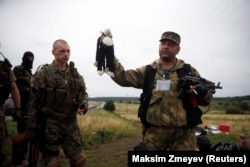 A pro-Russia separatist holds a stuffed toy found at the crash site of Malaysia Airlines flight MH17, near the settlement of Hrabove in the Donetsk region. (file photo)
