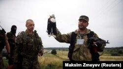 Пророссийский сепаратист держит в руках игрушку, надейденную близ крушения малайзийского самолета. Недалеко от села Грабово Донецкой области. 18 июля 2014 года.