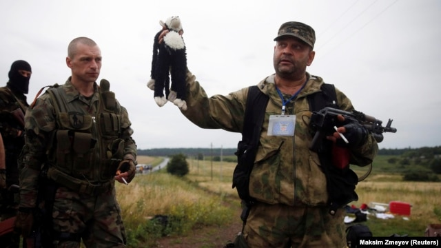 A pro-Russian separatist holds a stuffed toy found at the crash site of Malaysia Airlines Flight MH17 in eastern Ukraine on July 18.