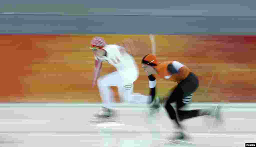 Нідерландець Роналд Мюлдер (п), який стане бронзовим медалістом, і росіянин Артем Кузнецов (л) у першому забігу швидкісного бігу на ковзанах на 500 м