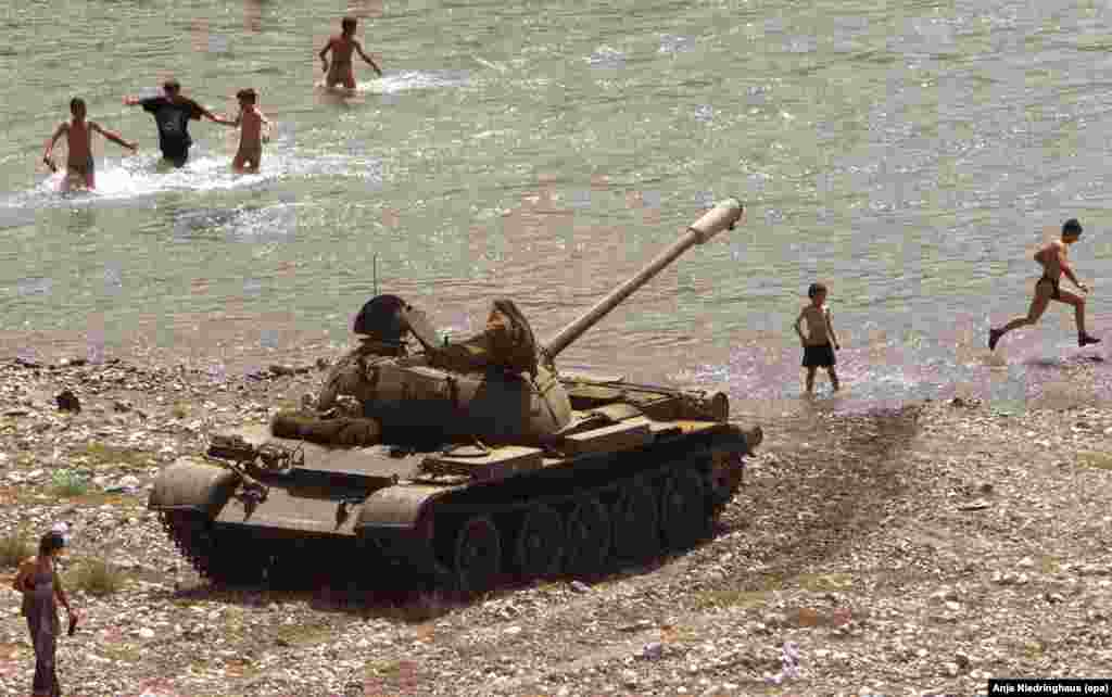 An Albanian army tank is positioned at the banks of a small lake near Kukes, Albania, on June 6, 1999, where ethnic Albanian refugees enjoy the beginning of summer.