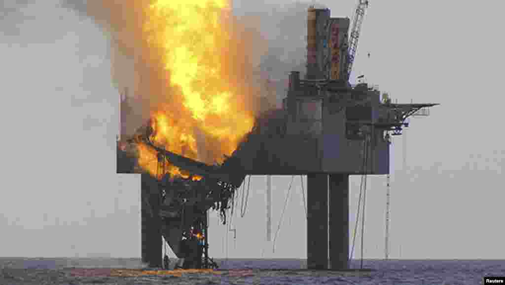 A shallow-water Gulf of Mexico drilling rig partially collapsed off the coast of Louisiana after catching fire because of a ruptured natural-gas well. The well released natural gas, but no oil, according to authorities. No one was on board when the rig caught fire. (Reuters)