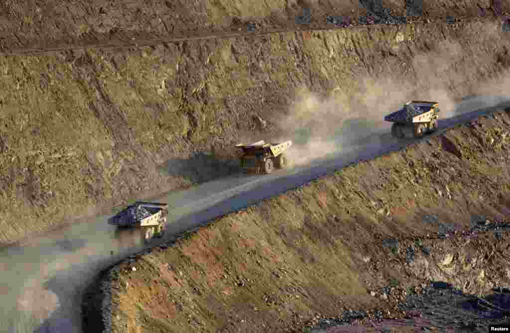 Near the extraction plant, trucks drive along a road at the Altyntau open pit gold mine.