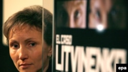 Marina Litvinenko stands by a poster for a documentary on the assassination of her husband.