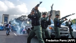 Members of the Bolivarian National Guard who joined Venezuelan opposition leader and self-proclaimed acting president Juan Guaido fire into the air to repel forces loyal to President Nicolas Maduro. April 30, 2019