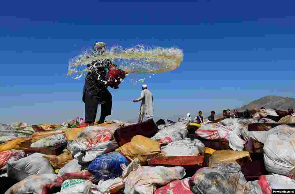 An Afghan man prepares to burn a pile of illegal narcotics on the outskirts of Jalalabad on September 26. (Reuters/Parwiz)