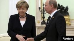 Президент России Владимир Путин протягивает руку канцлеру Германии Ангеле Меркель. Москва, 10 мая 2015 года.