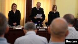 Inculpații (în prim plan), ascultând sentința curții de la Szeged
