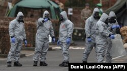 Military personnel wearing protective coveralls work to remove vehicles from a cordoned off area behind a police station in Salisbury following an attack on a former Russian spy by a nerve agent, which has now been identified as Novichok.