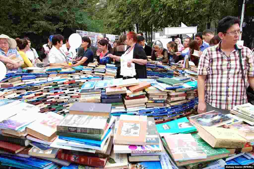 Многих посетителей привлекли разложенные высокими стопками и кругами старые книги, которые можно было выбрать и забрать домой для чтения. Алматы, 16 августа 2014 года.