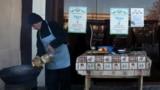 Повар в кафе в населенном пункте в Ташкентской области. На заднем плане - плакаты с информацией о выборах 4 декабря.