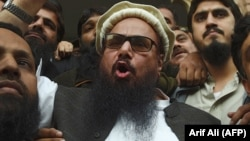 The head of the Pakistani Jamaat-ud-Dawa organization, Hafiz Saeed, speaks to the media after his release order outside a court in Lahore on November 22.