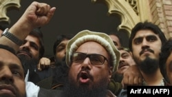 FILE: Pakistani head of the Jamaat-ud-Dawa (JuD) organization Hafiz Saeed (C) speaks to the media after his release order outside a court in Lahore in November 2017.