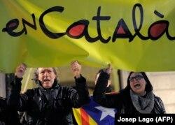 Дэманстранты трымаюць плякат з надпісам «па-каталянску» падчас пратэсту ў 2012 годзе супраць плянаў тагачаснага ўраду Гішпаніі правесьці моўную рэформу ў рэгіёне