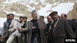 Afghan First Vice President Muhammad Qasim Fahim (right, in hat) tours and avalanche site in the Salang Pass, north of Kabul, with President Hamid Karzai (center) in 2010.