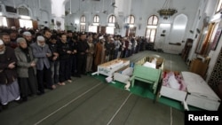 Mourners pray next to the bodies of victims of the violence during their funerals in Port Said.