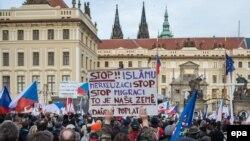 Участники антимусульманской акции держат плакат с надписью на чешском языке: «Остановите ислам и остановите Меркель». Прага, 6 февраля 2016 года.