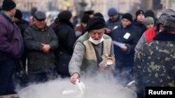 Мужчина готовит еду для протестующих на Майдане Незалежности. Киев, 5 декабря 2013 года.