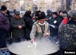Тәуелсіздік алаңында наразылық білдірушілерге тамақ әзірлеп жатқан адам. Киев, 5 желтоқсан 2013 жыл.