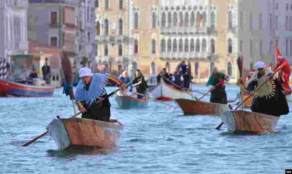 "Gondolieri dressed up as ""Befane"" (old women) steer their boats during a regatta on Venice's Grand Canal as part of Epiphany celebrations on January 6. (epa/Andrea Merola)"