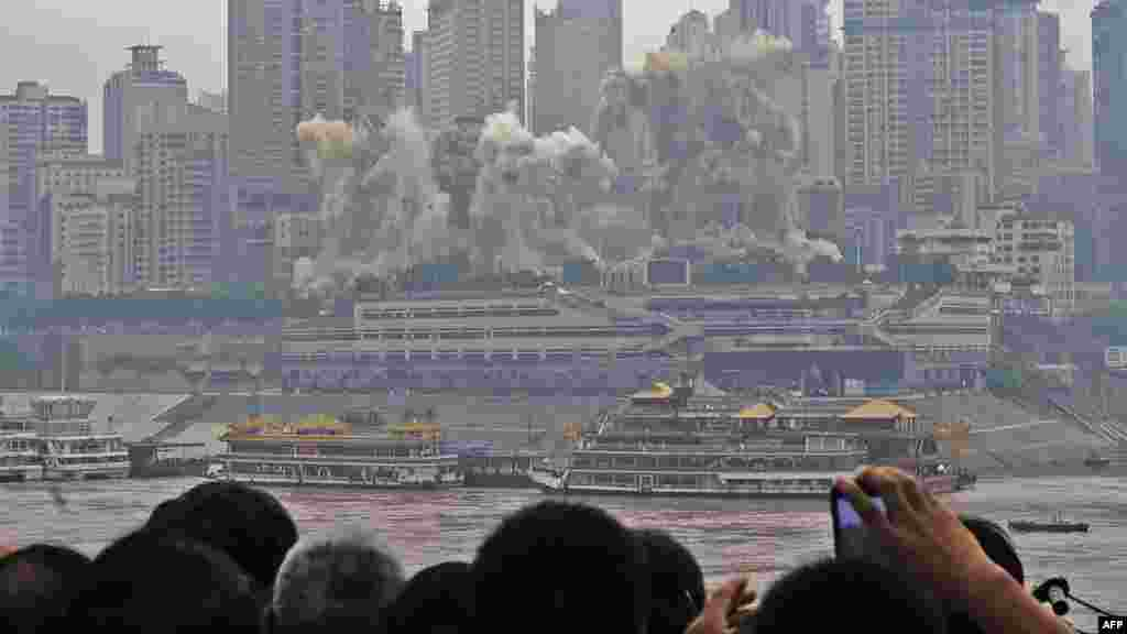 Residents watch as the Three Gorges Hotel and 32-story passenger terminal of Chongqing port are toppled in a controlled explosion to make way for new skyscrapers in southwest Chongqing municipality. (AFP PHOTO)