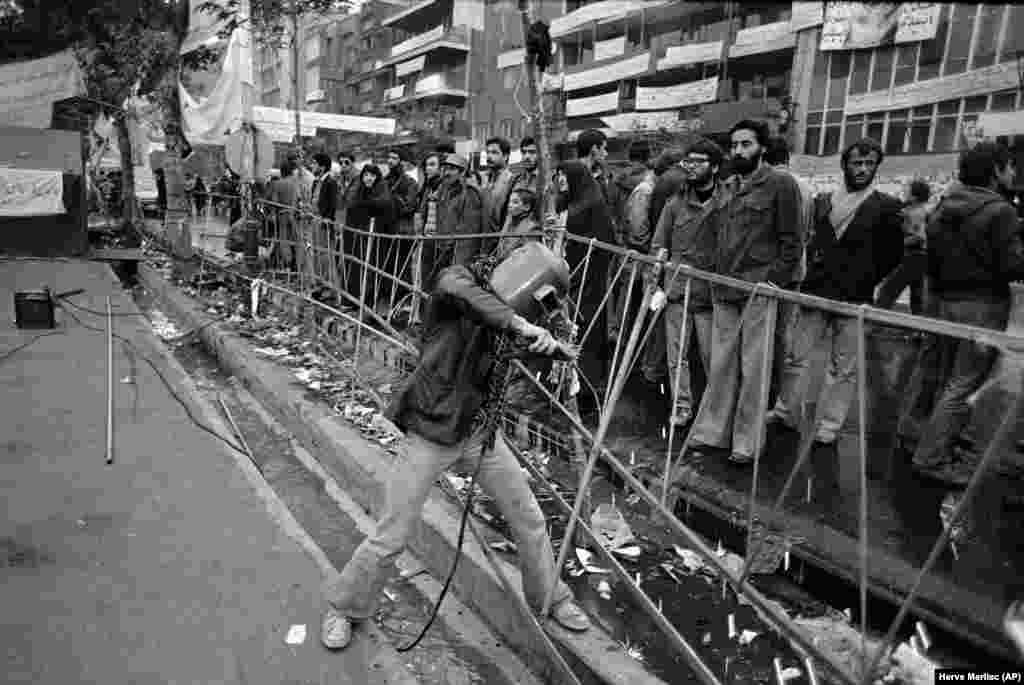 Чтобы сдержать натиск растущего числа участников антиамериканских акций, у ворот посольства установили металлическое ограждение. На фото – антиамериканская демонстрация 29 марта 1979 года, в день, когда иранцы отмечали праздник Тасуа.