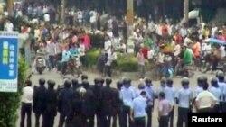 Гуанжоу шаарына жакын жерде тополоң салган мигрант жумушчулар менен коопсуздук күчтөрүнүн кагылышынан кийинки полиция тосмосу, 12-июнь.