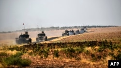 Turkish Army tanks drive near the Syrian border after the August launch of the military campaign.