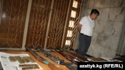 Kyrgyz officials display weapons seized in the arrests.