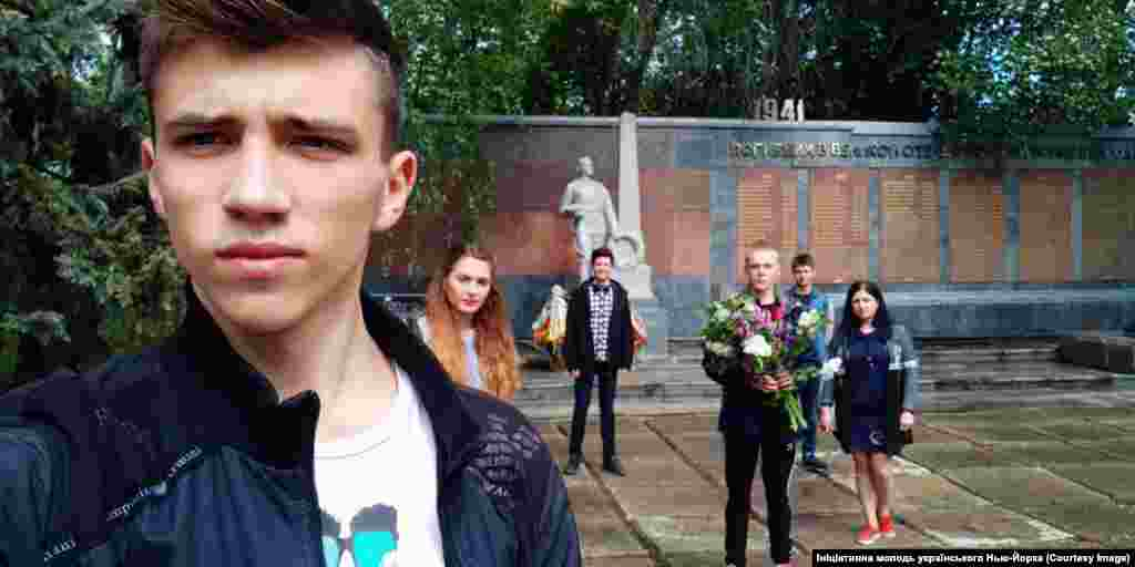 """Young locals pay their respects at one of Novhorodske's war memorials.  Shevchenko added: """"We are very much waiting for a positive decision from parliament. We overcame a difficult and thorny path to have our history heard."""""""