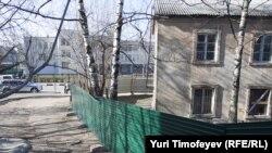 Жилой дом в Лыткарино напротив колледжа (на заднем плане), который собирается посетить Дмитрий Медведев, загородили от глаз президента большим зеленым забором
