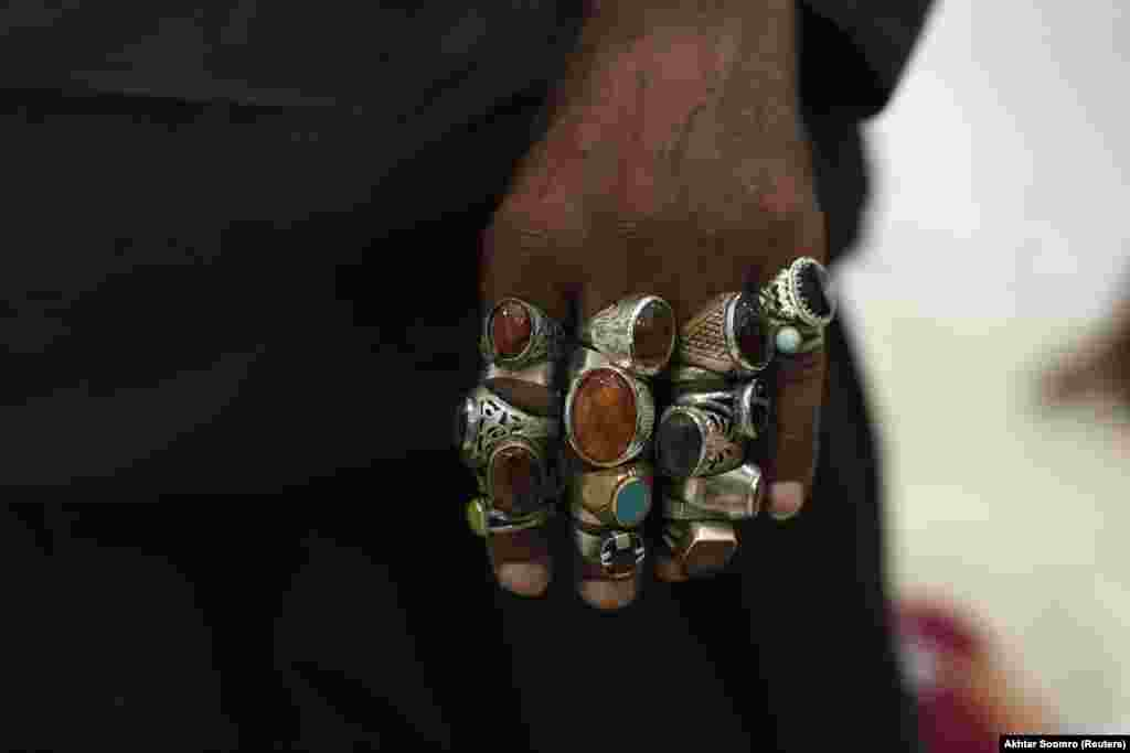 A devotee's hand is pictured decorated with rings inside the shrine. The annual festival is a spectacular parade of colorful clothing and personal decorations.