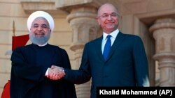 File photo - Iraqi President Barham Salih (right) stands with Iranian President Hassan Rohani during a welcome ceremony at Salam Palace in Baghdad, March 11, 2019