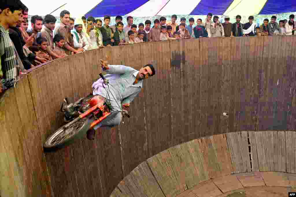 """A circus performer rides a motorcycle on the """"Wall of Death"""" at a fair on the second day of Eid al-Fitr in Jalalabad, Afghanistan. (AFP/Noorullah Shirzada)"""