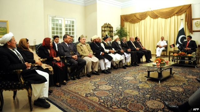 Pakistani Prime Minister Raja Pervez Ashraf (right) talks to members of the Afghan High Peace Council, which is chaired by Salahuddin Rabbani, in Islamabad on November 12.