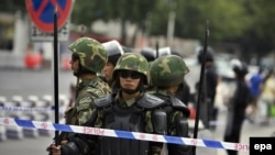 Chinese security forces armed with spears stand guard on People's Square after an incident between ethnic Uyghurs and Chinese security forces on the streets of Urumqi in July.