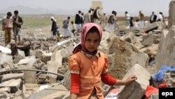 یک دختر یمنی در کنار خرابههای باقیمانده از محل سکونتش که هدف حملات هوایی ائتلاف به رهبری عربستان قرار گرفت