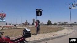 """""""Ислам мемлекеті"""" ұйымы содырларының қолына өткен Рамади қаласындағы аудандардың біріне содырдың ұйым туын тігіп жатқаны туралы видеодан скриншот. 18 мамыр 2015 жыл."""