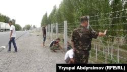 Ўзбек-қирғиз чегарасини тиконли сим билан тўсаётган чегарачилар.