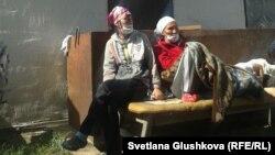 Две женщины сидят во дворе дома Алтын Червалиевой, который собираются снести. Астана, 8 августа 2014 года.