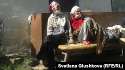 Две участницы голодовки сидят перед забаррикадированным входом в дом Алтын Червалиевой, который попадает под снос. Астана, 8 августа 2014 года.