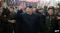 North Korean leader Kim Jong Un (center) is shown reportedly celebrating the successful test-firing of an intercontinental ballistic missile at an undisclosed location in this photograph released by North Korea's official Korean Central News Agency on July 5.