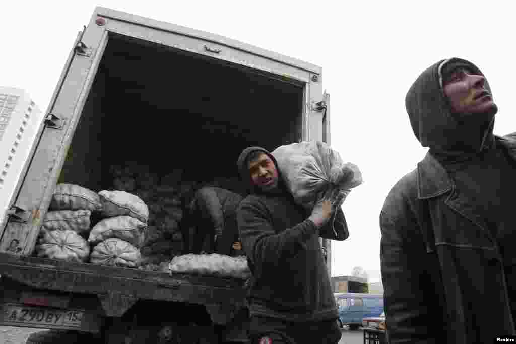 Мужчины разгружают мешки с картошкой на рынке. 2011.
