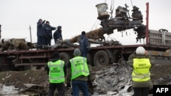 Members of the Dutch recovery and export team watch as Malaysia Airlines Flight 17 wreckage is loaded onto a truck near Hrabove in eastern Ukraine on November 16.