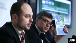 Vladimir Kara-Murza (left) holds up a copy of the report on corruption at the 2014 Sochi Olympics as Russian opposition leader Boris Nemtsov listens during a news conference on January 30, 2014, at the National Press Club in Washington, D.C.