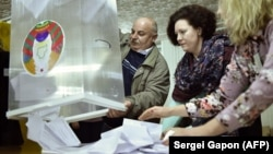 Members of a local election commission empty a ballot box to count votes at a polling station after the Belarusian parliamentary elections in the village of Kreva, outside Minsk, on November 17.