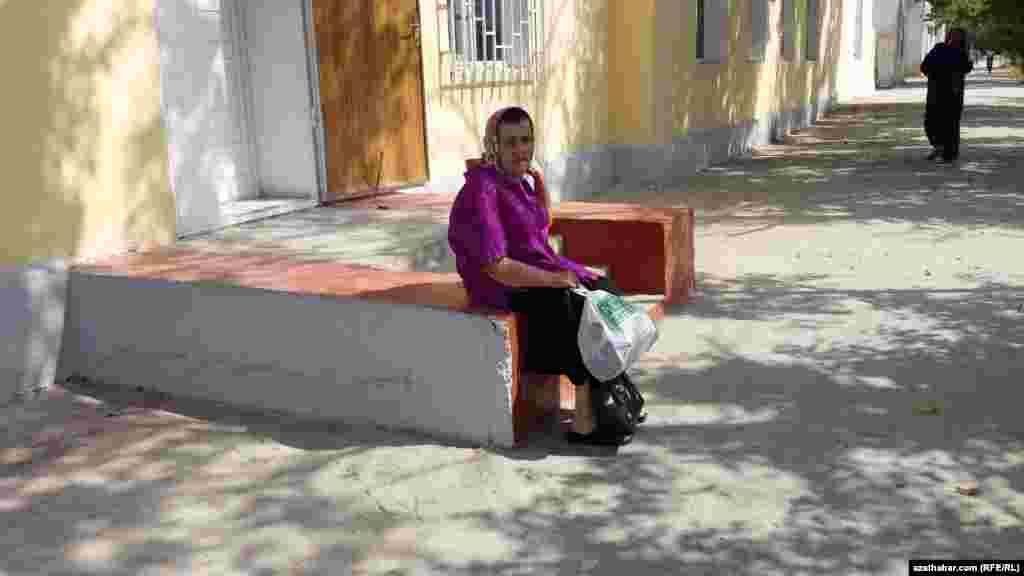 Balkanabat şäherinde bir binanyň daşyndaky basgançaklarda oturan garry ene.